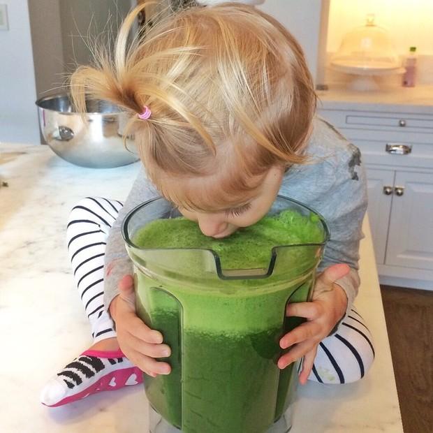 Vivian, filha da ubber model Gisele Bundchen, mergulhada em um suco verde